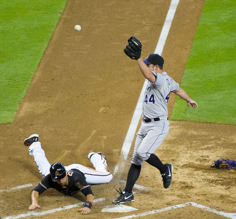 . Arizona Diamondbacks third baseman Eric Chavez slides in safely for a run after a wild pitch as Colorado Rockies pitcher Roy Oswalt (44) reaches for the throw in the bottom of the second of a baseball game Sunday, July 7, 2013, in Phoenix. (AP Photo/The Arizona Republic, Aaron Lavinsky)