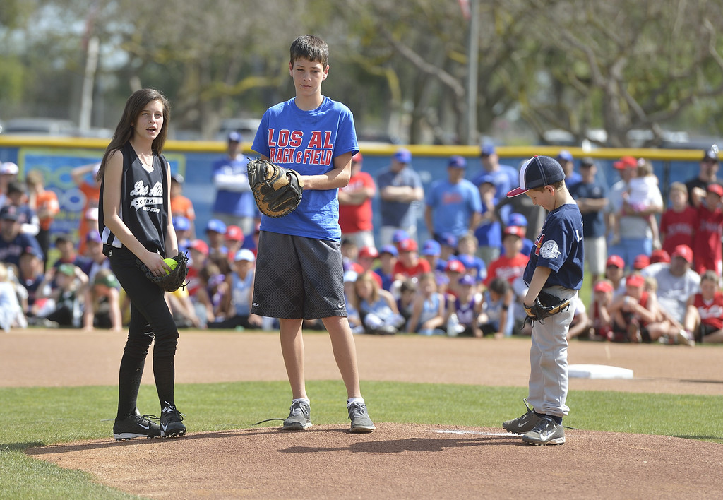 . LONG BEACH, CALIF. USA -- Makayla  Fowler, left, Andrew Fowler, center, and Jacob Fowler prepare to toss the first pitch during opening ceremonies for Los Altos Youth Baseball and Softball at El Dorado Park in Long Beach, Calif. on March 2, 2013. Throwing the first pitch to their father, league president Dwayne Fowler, was in honor of their mother, Colette Fowler who was in charge of the snack bar and was a huge part of the league. She died of cancer last September.    hugs his oldest son, Andrew Fowler, after Andrew delivered one of three first pitches during opening ceremonies at El Dorado Park in Long Beach, Calif. on March 2, 2013. Fowler\'s other children, Jacob Fowler and Makayla Fowler delivered the other first pitches. Their mother, Colette Fowler Photo by Jeff Gritchen / Los Angeles Newspaper Group