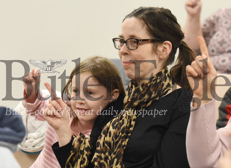 Olivia McAfee and her mother Katie practice signing with the rest of the introduction to sign language workshop attendees at the Zelienople Library Monday night. The library put on the what they hope might be a monthly class in conjunction with the Rose E. Schneider Family YMCA. Seb Foltz/Butler Eagle 01/13/20