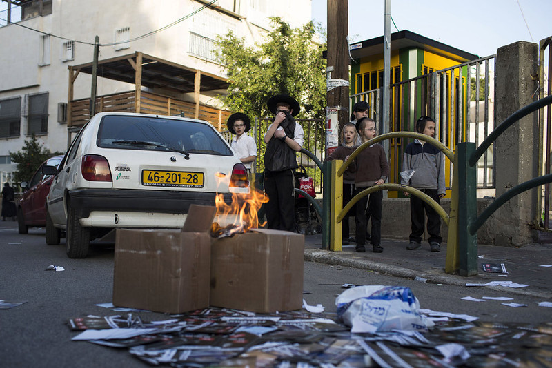 . Ultra-Orthodox Jewish children burn a Likud party election banner at the Yeshiva next to the polling station on January 22, 2013 in Bnei Brak, Israel. The latest opinion polls suggest that current Prime Minister Benjamin Netanyahu will return to office, albeit with a reduced majority.  (Photo by Ilia Yefimovich/Getty Images)