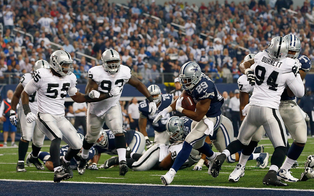 . DeMarco Murray #29 of the Dallas Cowboys scores a touchdown against  Sio Moore #55 of the Oakland Raiders and  Jason Hunter #93 of the Oakland Raiders during a Thanksgiving Day game at AT&T Stadium on November 28, 2013 in Arlington, Texas.  (Photo by Tom Pennington/Getty Images)
