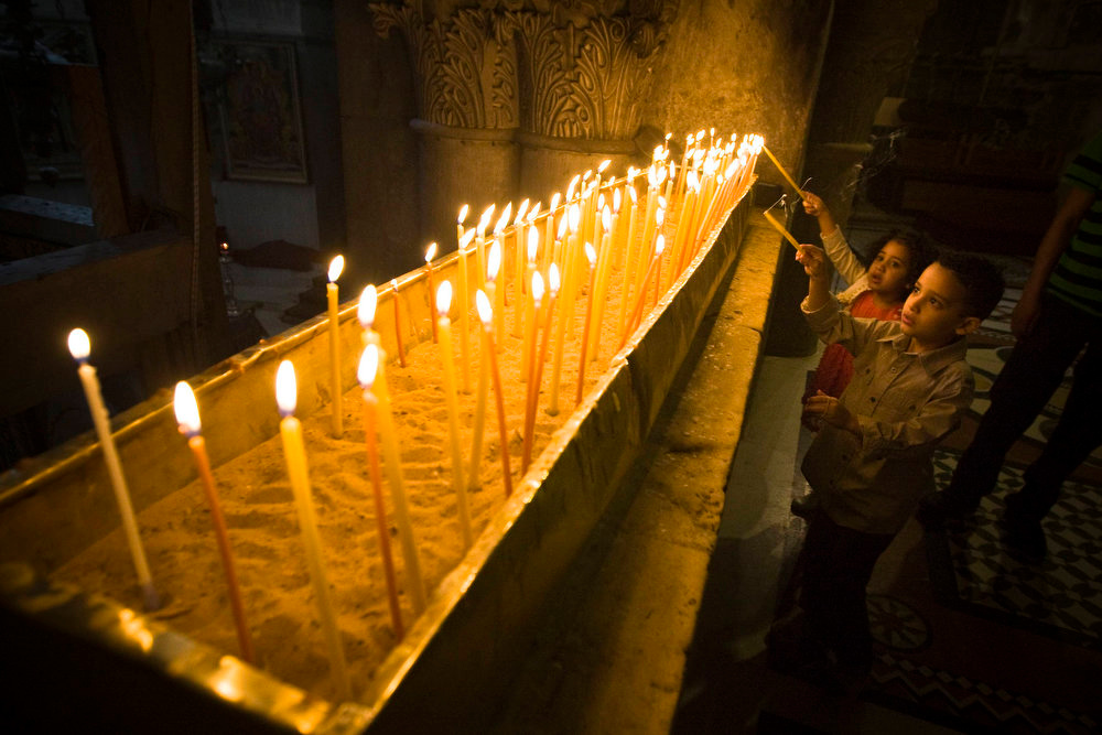 Description of . Young worshippers light candles during Easter Sunday mass at the Church of the Holy Sepulchre in Jerusalem's Old City March 31, 2013.  REUTERS/Amir Cohen