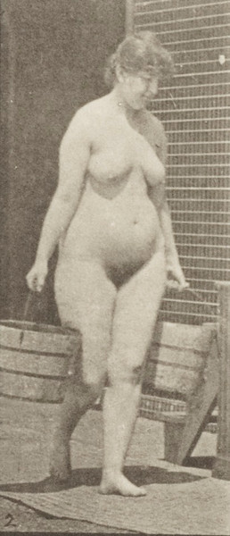 Nude woman turning to ascend stairs with a bucket of water