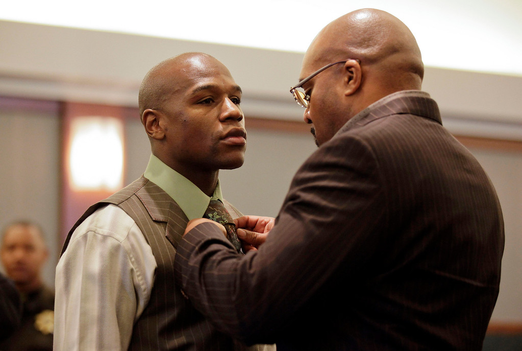 . Boxer Floyd Mayweather Jr., left, has his tie adjusted by his manager Leonard Ellerbe while waiting for sentencing in Clark County District Court, Wednesday, Dec. 21, 2011, in Las Vegas. Mayweather was sentenced to 90 days in jail after pleading guilty to reduced battery domestic violence and harassment charges. The 34-year-old was also ordered to complete 100 hours of community service and pay a $2,500 fine. The plea deal avoids trial on felony allegations that he hit his ex-girlfriend and threatened two of their children during an argument at her home in September 2010. (AP Photo/Julie Jacobson)
