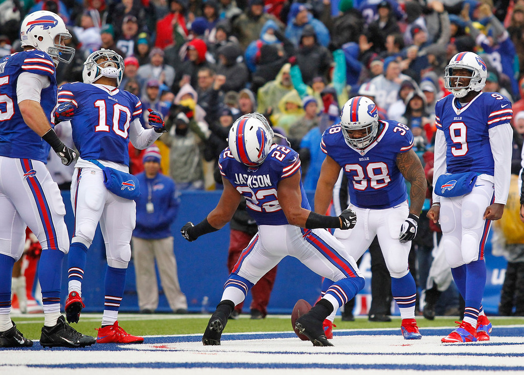 . Buffalo Bills running back Fred Jackson (22) celebrates his touchdown with teammates Lee Smith (85), Robert Woods (10), Frank Summers (38) and Thad Lewis (9) during the first half of an NFL football game against the Miami Dolphins on Sunday, Dec. 22, 2013, in Orchard Park, N.Y. (AP Photo/Bill Wippert)
