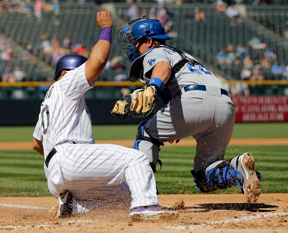 . Los Angeles Dodgers catcher Tim Federowicz, right, tags out Colorado Rockies\' Wilin Rosario, left, at home plate during the first inning of a baseball game Wednesday, Sept. 17, 2014, in Denver. (AP Photo/Jack Dempsey)
