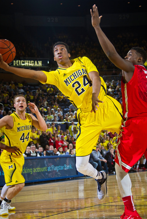 . Michigan guard Aubrey Dawkins (24) attempts a hook shot under the basket while defended by Ohio State forward Jae\'Sean Tate, right, in the second half of an NCAA college basketball game in Ann Arbor, Mich., Sunday, Feb. 22, 2015. Michigan won 64-57. (AP Photo/Tony Ding)