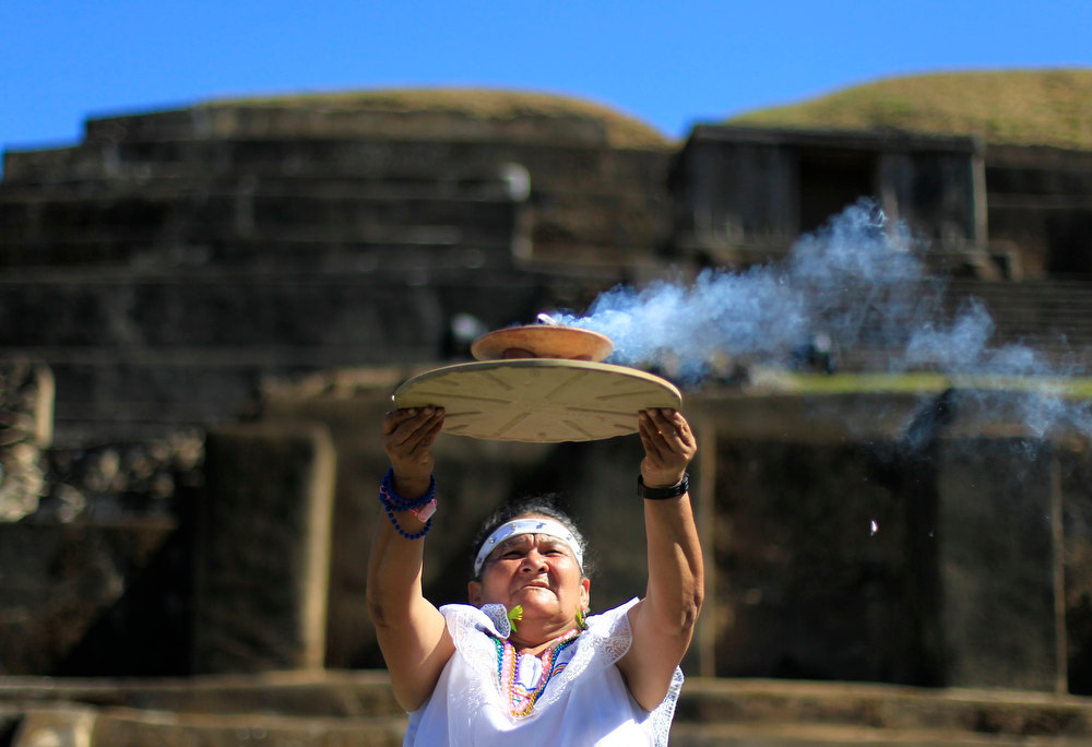 Description of . Mayte Dominuez, shaman of the town of Cuisnahuat, holds up the sacred fire during a ceremony at the Maya archeological site of Tazumal in Santa Ana, about 75 km (47 miles) away from San Salvador, El Salvador, December 21, 2012. Mystics, hippies and tourists descended on the ruins of Maya cities to mark the close of the 13th bak'tun - a period of around 400 years - and many hoped it would lead to a better era for humanity. This week, at sunrise on Friday, December 21, an era closes in the Maya Long Count calendar, an event that has been likened by different groups to the end of days, the start of a new, more spiritual age or a good reason to hang out at old Maya temples across Mexico and Central America.  REUTERS/Ulises Rodriguez