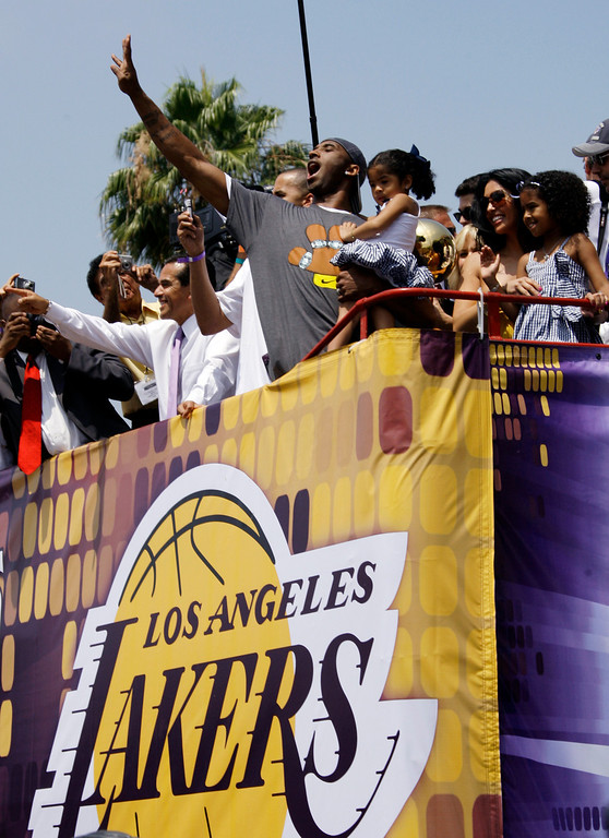 . Los Angeles Lakers\' Kobe Bryant waves, while holding his daughter Gianna Maria-Onore, while his wife Vanessa, second from right, and their daughter Natalia Diamante, right, look on as Los Angeles Mayor Antonio Villaraigosa, left, waves as Lakers NBA basketball world championship parade gets underway in Los Angeles, Wednesday, June 17, 2009  (AP Photo/Reed Saxon)