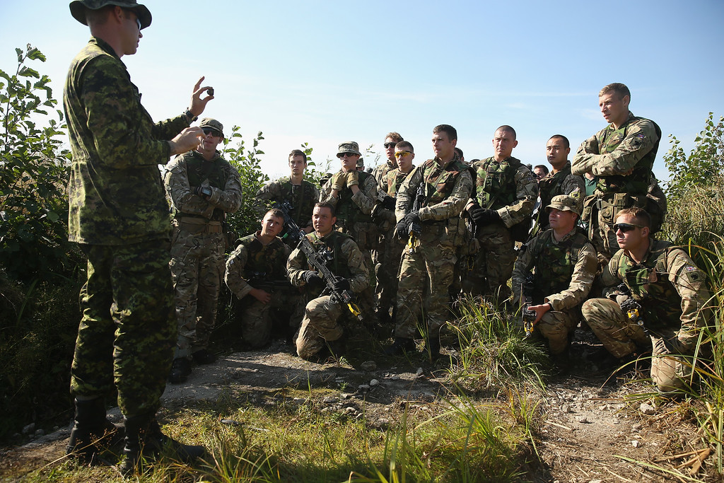 ". Members of the British Light Dragoons receive instruction in anti-IED (improvised explosive device) location and removal from a Canadian soldier (L) on the second day of the ""Rapid Trident\"" NATO military exercises on September 16, 2014 near Yavorov, Ukraine.  (Photo by Sean Gallup/Getty Images)"