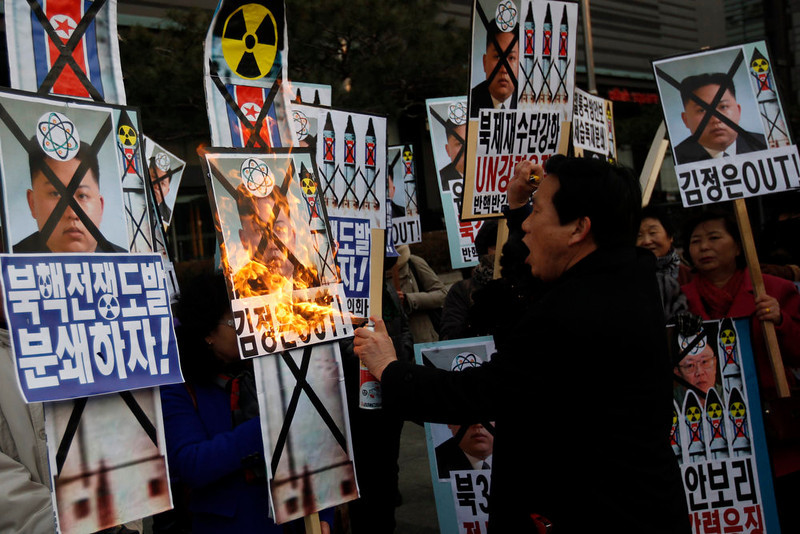 ". An activist from an anti-North Korea civic group burns a portrait of North\'s leader Kim Jong-un during a rally against North Korea\'s nuclear test near the U.S. embassy in central Seoul February 12, 2013.  North Korea conducted its third nuclear test on Tuesday in defiance of U.N. resolutions, angering the United States and Japan and prompting its only major ally, China, to call for calm. The placards read, ""Let\'s pulverize North Korea\'s nuclear war provocations!\"" (L) and \""Kim Jong-un out!\"" (R) REUTERS/Kim Hong-Ji"