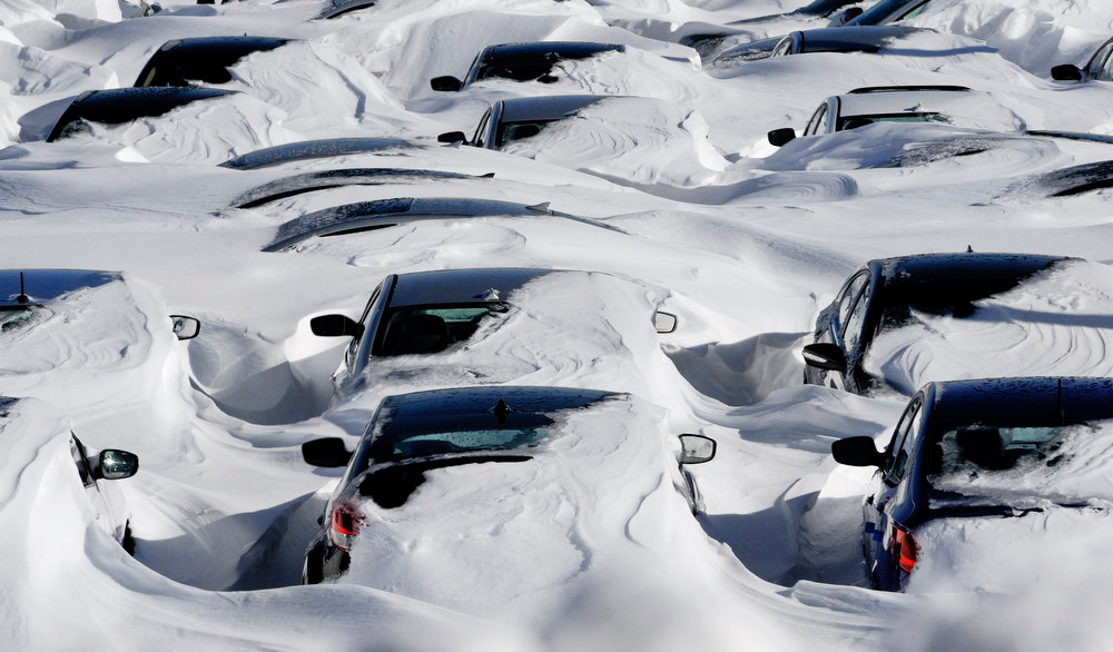 . Snow begins to melt on cars parked at a dealership after a winter storm in Hartford, Conn., Sunday, Feb. 10, 2013.  A howling storm across the Northeast left much of the New York-to-Boston corridor covered with more than three feet of snow on Friday into Saturday morning. (AP Photo/Jessica Hill)