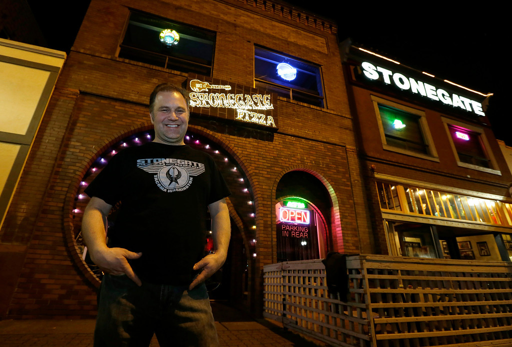 ". Jeff Call, owner of the Stonegate pizza-and-rum bar, poses for a photo in front of his business, Saturday, March 2, 2013, in Tacoma, Wash. Call charges patrons a small fee to become a member of the private second-floor club in the lounge area upstairs, which allows ""vaporizing,\"" marijuana, a method that involves heating the marijuana without burning it. Last fall, Washington and Colorado became the first states to legalize marijuana use for adults over 21. (AP Photo/Ted S. Warren)"