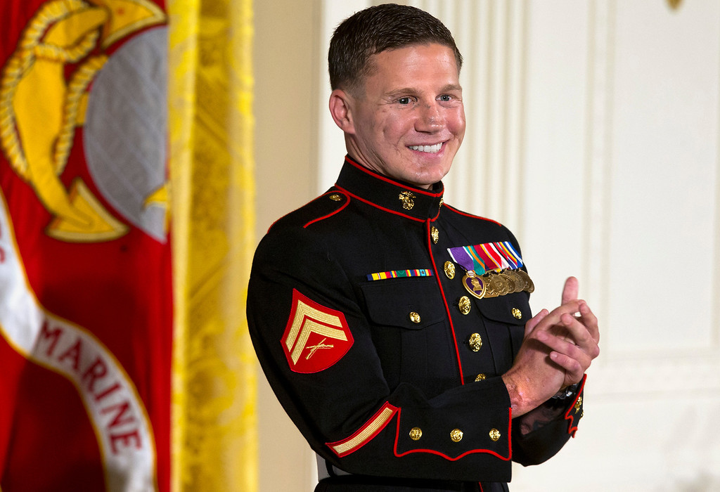". Retired Marine Cpl. William ""Kyle\"" Carpenter applauds his medical team as they stand to be acknowledged by President Barack Obama during a ceremony presenting Carpenter with the Medal of Honor for conspicuous gallantry, Thursday, June 19, 2014, in the East Room of the White House in Washington. Carpenter received the Medal of Honor for his courageous actions while serving as an Automatic Rifleman in Helmand Province, Afghanistan. (AP Photo/Jacquelyn Martin)"