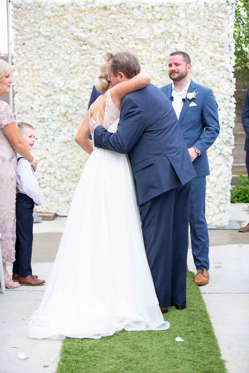 a father hugging his daughter after he walked her down the aisle at her wedding