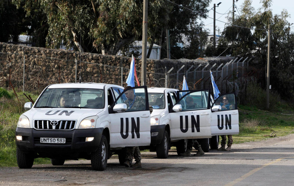 . United Nations peacekeepers put on protective gear before driving through the Kuneitra border crossing between Israel and Syria, in the Israeli occupied Golan Heights March 8, 2013. Israel voiced confidence on Thursday that the United Nations could secure the release of U.N. peacekeepers seized by Syrian rebels near the Golan Heights on Wednesday, signaling it would not intervene in the crisis. Israel captured the Golan Heights in the 1967 Middle East war and annexed it in 1981 in a move not recognized internationally. REUTERS/Baz Ratner