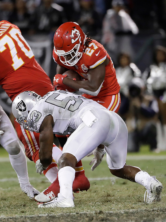 . Oakland Raiders linebacker NaVorro Bowman (53) tackles Kansas City Chiefs running back Kareem Hunt (27) during the second half of an NFL football game in Oakland, Calif., Thursday, Oct. 19, 2017. (AP Photo/Marcio Jose Sanchez)