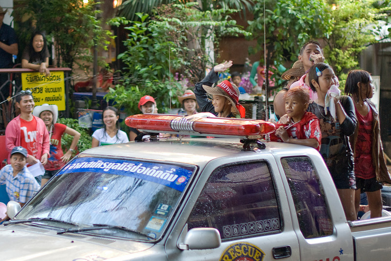 Kids riding behind medic truck at the Songkran Festival in Thailand
