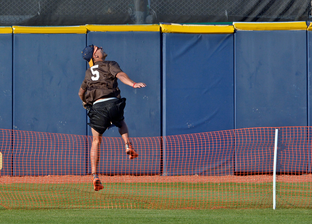 . Jeff Forman/JForman@News-Herald.com Jordan Poyer hops over the fence to chase a home run during the Joe Haden and Friends Softball Game July 17 at Classic Park.