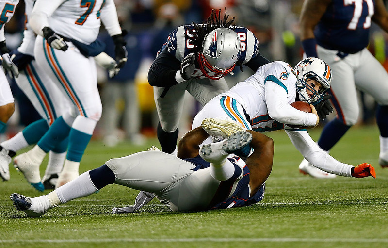 . Ryan Tannehill #17 of the Miami Dolphins is sacked by Justin Francis #94 and Jermaine Cunningham #96 of the New England Patriots in the second half during the game at Gillette Stadium on December 30, 2012 in Foxboro, Massachusetts. (Photo by Jared Wickerham/Getty Images)