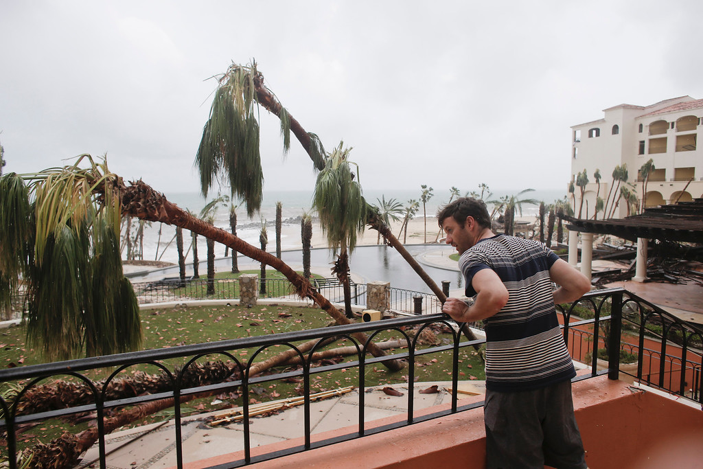 . Tourist Patrick Egan from California looks at the interior patios of the Hilton hotel, damaged by Hurricane Odile in Los Cabos, Mexico, Monday, Sept. 15, 2014. (AP Photo/Victor R. Caivano)