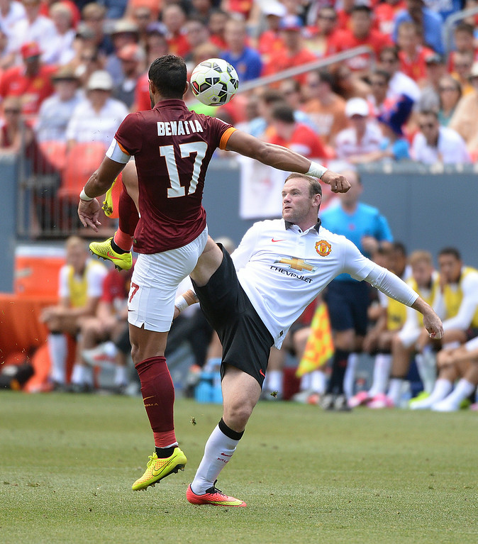 . Manchester United striker Wayne Rooney battled for the ball with AS Roma defender Mehdi Benatia in the first half. Manchester United took on AS Roma in an exhibition soccer game at Sports Authority Field in Denver Saturday afternoon, July 27, 2014. Photo by Karl Gehring/The Denver Post
