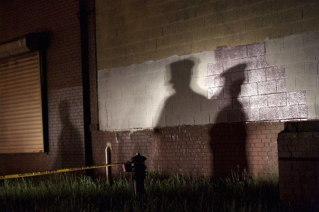 . PHILADELPHIA, PA - MAY 13:  The shadow of a police officer is cast onto a building near the wreckage of an Amtrak passenger train carrying more than 200 passengers from Washington, DC to New York that derailed May 13, 2015 in north Philadelphia, Pennsylvania. At least five people were killed and more than 50 others were injured in the crash.  (Photo by Mark Makela/Getty Images)