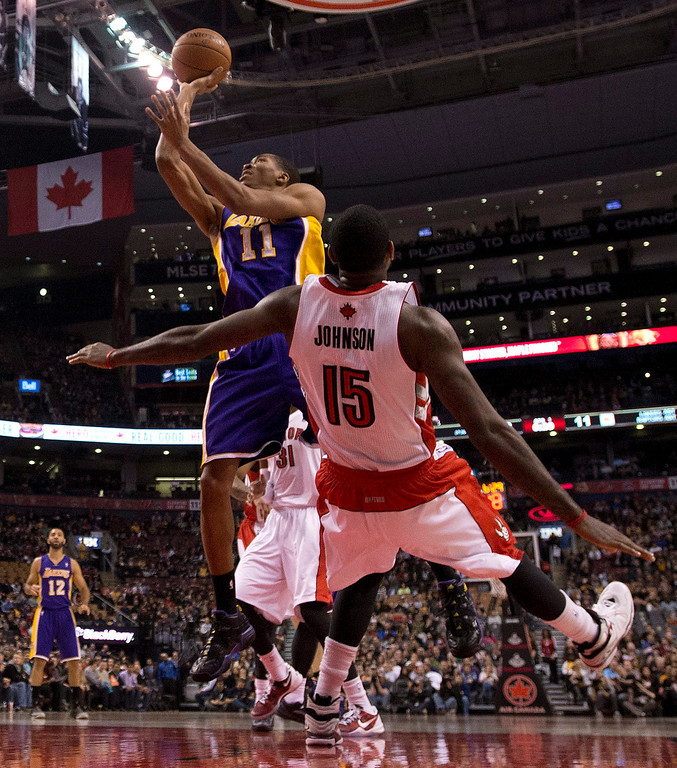 . Los Angeles Lakers forward Wesley Johnson (11) picks up an offensive fouls as he drives through Toronto Raptors forward Amir Johnson (15) during first-half NBA basketball game action in Toronto, Sunday, Jan. 19, 2014. (AP Photo/The Canadian Press, Frank Gunn)
