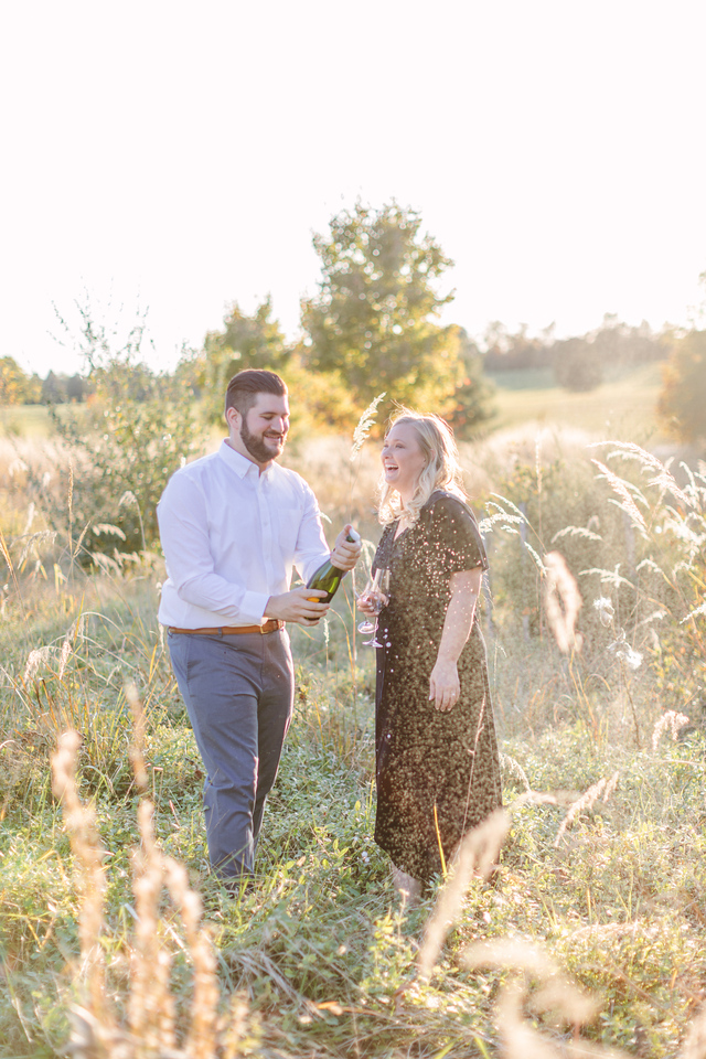 Popping the champagne at their field engagement session in Virginia.
