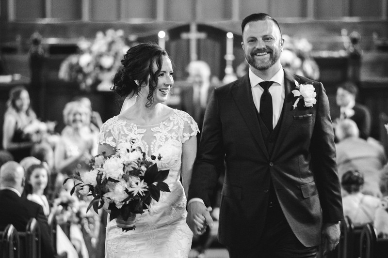 The bride smiling up at the groom as he smiles towards the camera as they walk hand in hand up the isle.