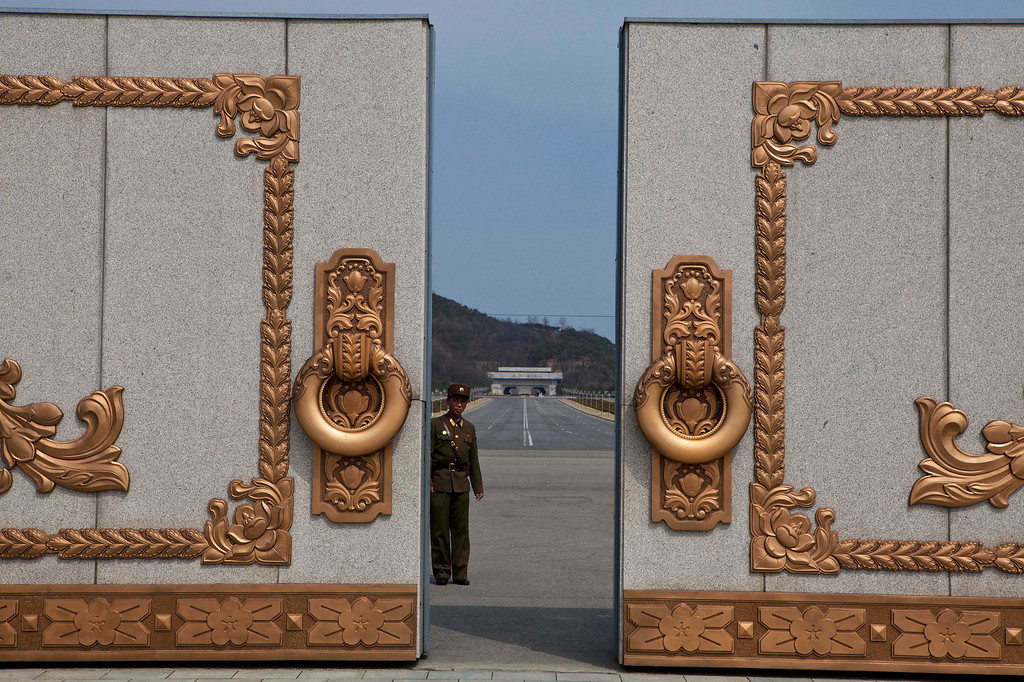. A North Korean soldier guarding the entrance to Pyongyang\'s Kumsusan mausoleum, where the bodies of the late leaders Kim Il Sung and Kim Jong Il lie embalmed, looks back through the doors of the main gate Monday, April 15, 2013. North Koreans turned out on Monday to mark the 101st birthday of Kim Il Sung. (AP Photo/David Guttenfelder)