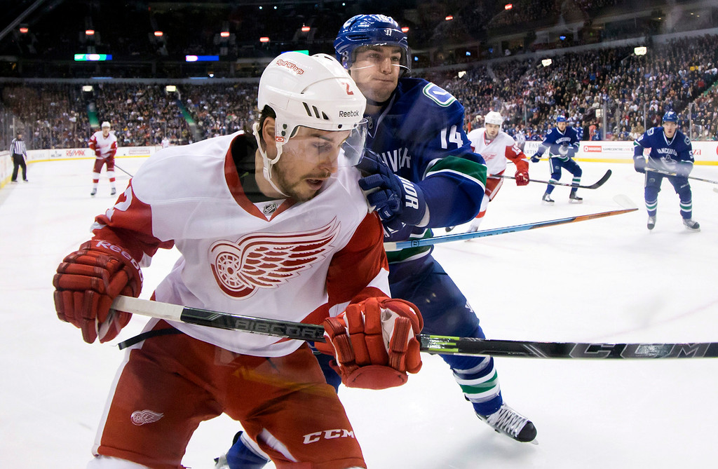 . Vancouver Canucks\' Alex Burrows, back, checks Detroit Red Wings\' Brendan Smith during the first period of an NHL hockey game in Vancouver, British Columbia on Saturday, Jan. 3, 2015. (AP Photo/The Canadian Press, Darryl Dyck)