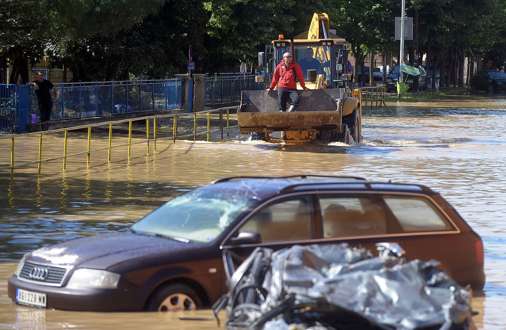 . A man rides on a bulldozer through flooded streets of the town of Obrenovac, 40 kilometres west of Belgrade, on May 19, 2014. The Balkans braced for more misery as the death toll from the worst floods in a century rose to 47 and rising waters forced thousands more to flee their homes. Muddy waters from the Sava River have submerged houses, churches, mosques and roads in Bosnia, Serbia and Croatia after record rainfall wreaked havoc across the central European region.  AFP PHOTO / ALEXA  STANKOVIC/AFP/Getty Images