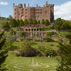 View over the grass maze to the terraces and south front at Powis Castle and Garden, Powys, in August.