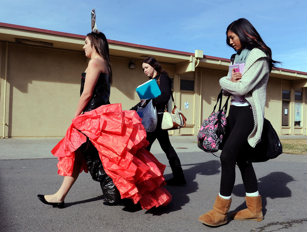 . Concerned with the durability of their creation, designers Jayden Tolentino, right, and Tara Traglin keep a close eye on Lacey Lopez who heads to the Performing Arts Center to model her high low skirt at the third annual Paper Skirt Fashion Show held at Liberty High School in Brentwood, Calif.  on Tuesday, Jan. 29, 2013. (Susan Tripp Pollard/Staff)
