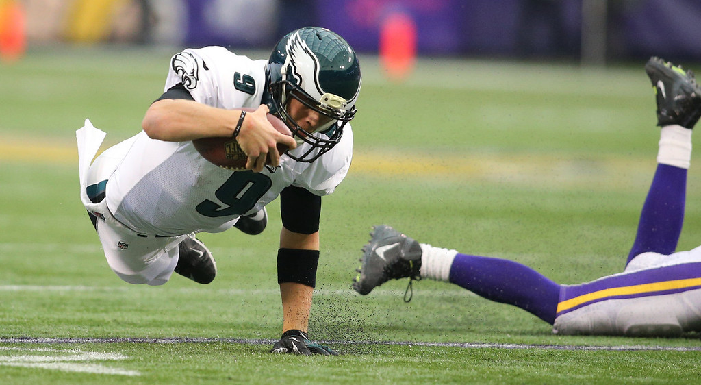 . Nick Foles #9 of the Philadelphia Eagles dives for a gain against the Minnesota Vikings on December 15, 2013 at Mall of America Field at the Hubert H. Humphrey Metrodome in Minneapolis, Minnesota. (Photo by Adam Bettcher/Getty Images)