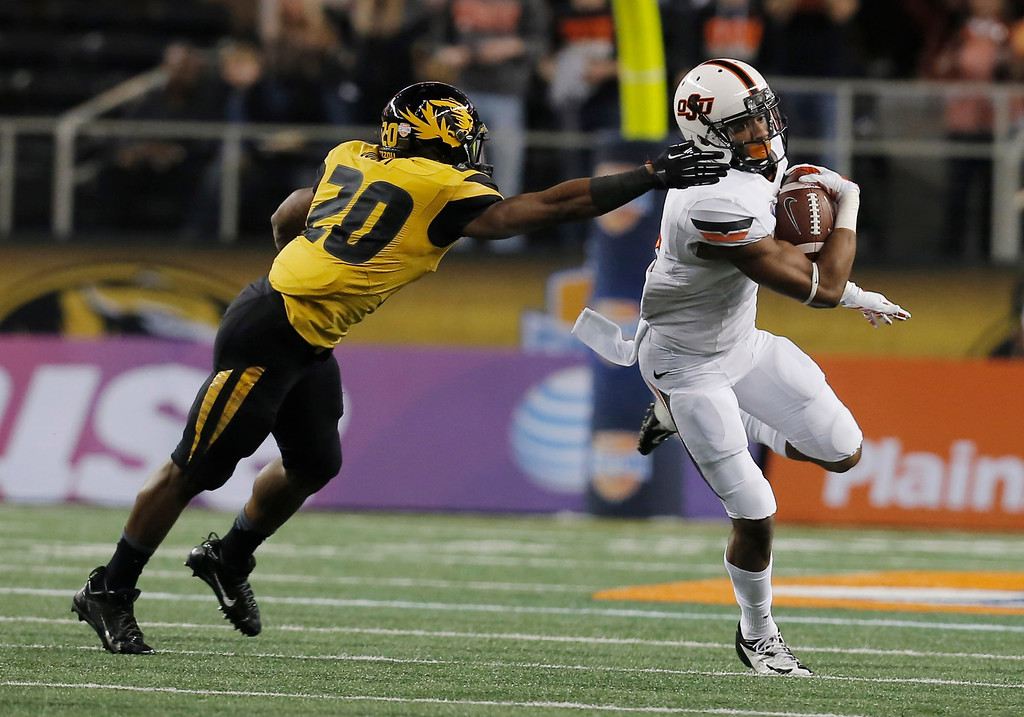 . After intercepting the ball from Missouri quarterback James Franklin, Oklahoma State cornerback Justin Gilbert (4) gets past Missouri running back Henry Josey (20) during the first half of the Cotton Bowl NCAA college football game on Friday, Jan. 3, 2014, in Arlington, Texas. (AP Photo/Brandon Wade)