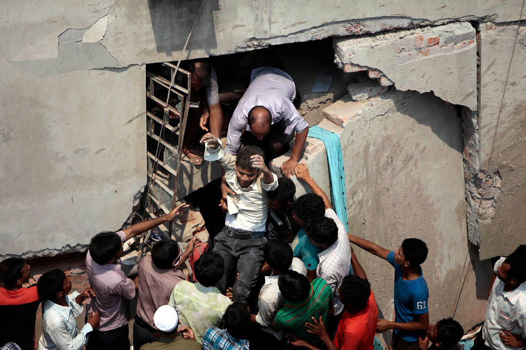 . A man who was trapped in an eight-story building housing several garment factories is rescued after the structure collapsed in Savar, near Dhaka, Bangladesh, Wednesday, April 24, 2013. The building collapsed near Bangladesh\'s capital Wednesday morning, killing dozens of people and trapping many more in the rubble, officials said. (AP Photo/ A.M. Ahad)