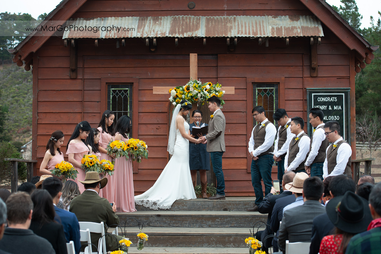 bride and groom holding hands and praying during wedding ceremony at Long Branch Saloon & Farms in Half Moon Bay