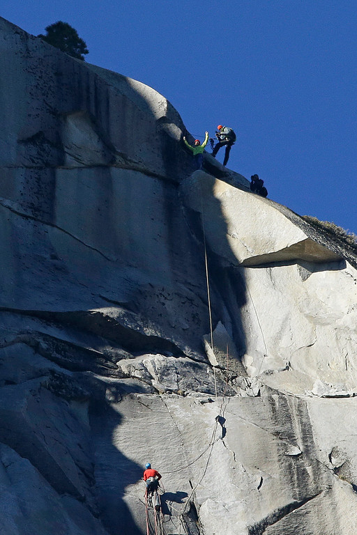 . Tommy Caldwell, top, raises his arms after reaching the summit of El Capitan as Kevin Jorgeson, bottom, watches Wednesday, Jan. 14, 2015, as seen from the valley floor in Yosemite National Park, Calif. Caldwell and Jorgeson became the first to free-climb the rock formation\'s Dawn Wall. They used ropes and safety harnesses to catch them in case of a fall, but relied entirely on their own strength and dexterity to ascend by grasping cracks as thin as razor blades and as small as dimes. The effort took 19 days, as the two dealt with constant falls and injuries. (AP Photo/Ben Margot)
