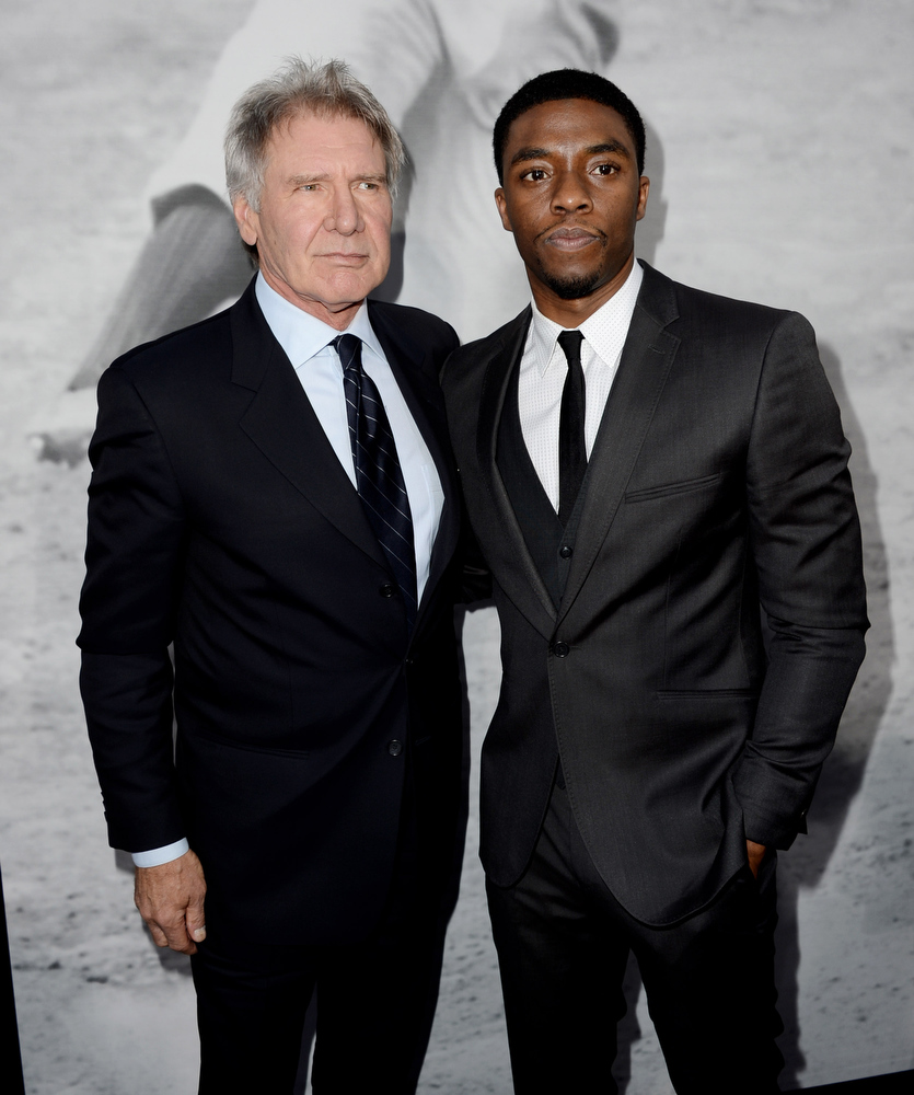 ". Actors Harrison Ford (L) and Chadwick Boseman arrive at the premiere of Warner Bros. Pictures\' and Legendary Pictures\' ""42\"" at the Chinese Theatre on April 9, 2013 in Los Angeles, California.  (Photo by Kevin Winter/Getty Images)"