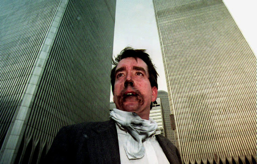 Description of . Brian Rolchford stands outside the World Trade Center after walking down from the 105th floor. Smoke swept through the 110-story building after an explosion caused the ceiling of a train station to collapse on February 26, 1993. The explosion set off a fire below the twin towers. (TIM CLARY/AFP/Getty Images)
