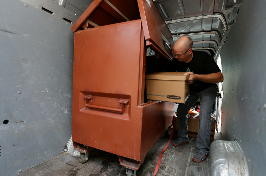 . Phil Tobias, director of Sea of Green Farms, loads boxes of recreational marijuana into a lockbox inside a van, Tuesday, July 8, 2014, in Seattle, for delivery to a store in Bellingham, Wash. It was the first delivery for the company since retail licenses were issued by the state on Monday. (AP Photo/Ted S. Warren)