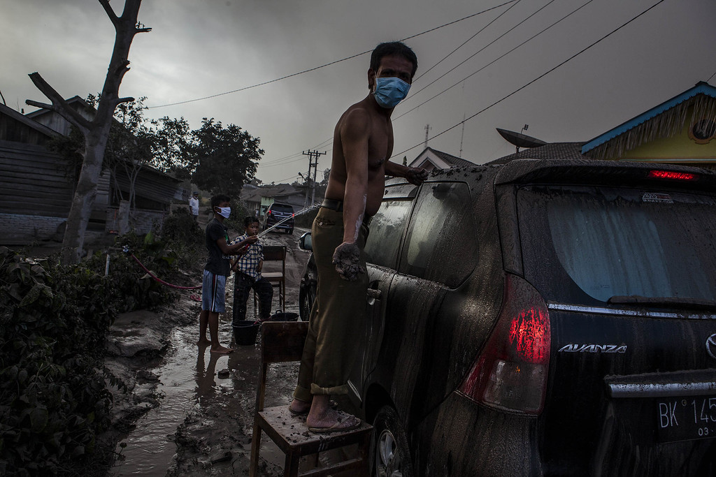. A man cleans his car as their village is hit by ash from the eruption of Mount Sinabung on October 13, 2014 in Berastagi, Karo district, North Sumatra, Indonesia.  (Photo by Ulet Ifansasti/Getty Images)