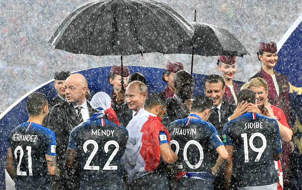 . FIFA President Gianni Infantino, Russian President Vladimir Putin, French President Emmanuel Macron and Croatian President Kolinda Grabar-Kitarovic, from left, stand in the puring rain as they congratulate the French players after France won 4-2 in the final match between France and Croatia at the 2018 soccer World Cup in the Luzhniki Stadium in Moscow, Russia, Sunday, July 15, 2018. (AP Photo/Martin Meissner)