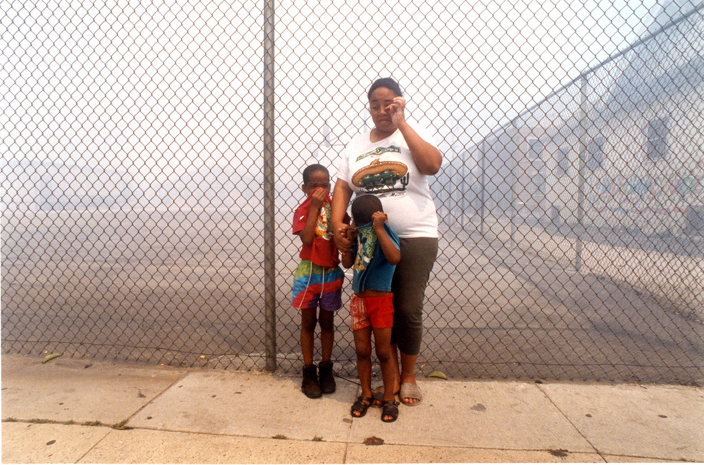 . Tracia Jyles and her sons, Dionte, 6, left, and Tony, 3, wipe tears from their eyes caused by smoke from a nearby fire on 56th Street and Vermont Ave. in South Central Los Angeles. (Los Angeles Daily News file photo)