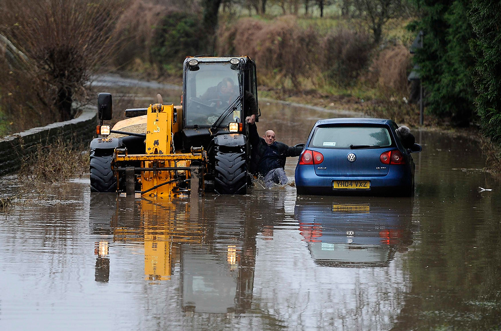 . A man climbs from his stranded vehicle in flood water at Milby, northern England on December 21, 2012. More rain was forecast overnight on Friday, with more than 260 flood alerts and about 75 flood warnings issued during a period of wet weather, local media reported.   REUTERS/Nigel Roddis