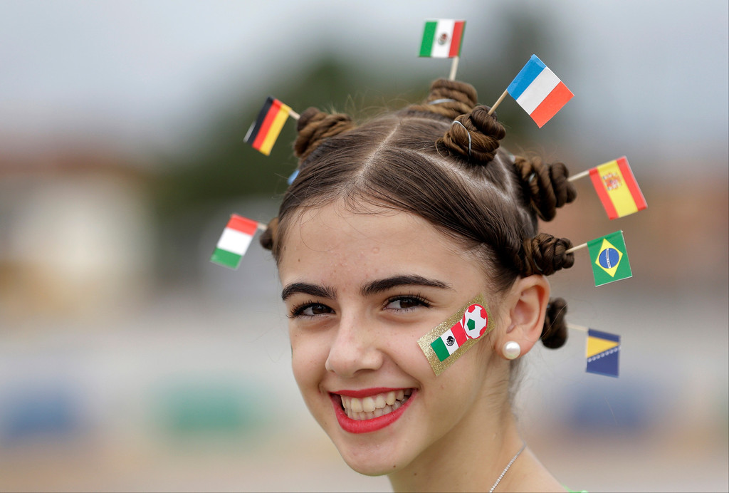 . A fan donning miniature national flags representing Italy, Germany, Mexico, the Netherlands, Spain, Brazil and Bosnia in her hair smiles, prior to the group A World Cup soccer match between Brazil and Mexico at the Arena Castelao in Fortaleza, Brazil, Tuesday, June 17, 2014.  (AP Photo/Themba Hadebe)