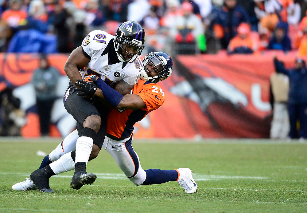 Description of . Denver Broncos cornerback Champ Bailey (24) makes a tackle on Baltimore Ravens wide receiver Anquan Boldin (81) in the second quarter. The Denver Broncos vs Baltimore Ravens AFC Divisional playoff game at Sports Authority Field Saturday January 12, 2013. (Photo by AAron  Ontiveroz,/The Denver Post)