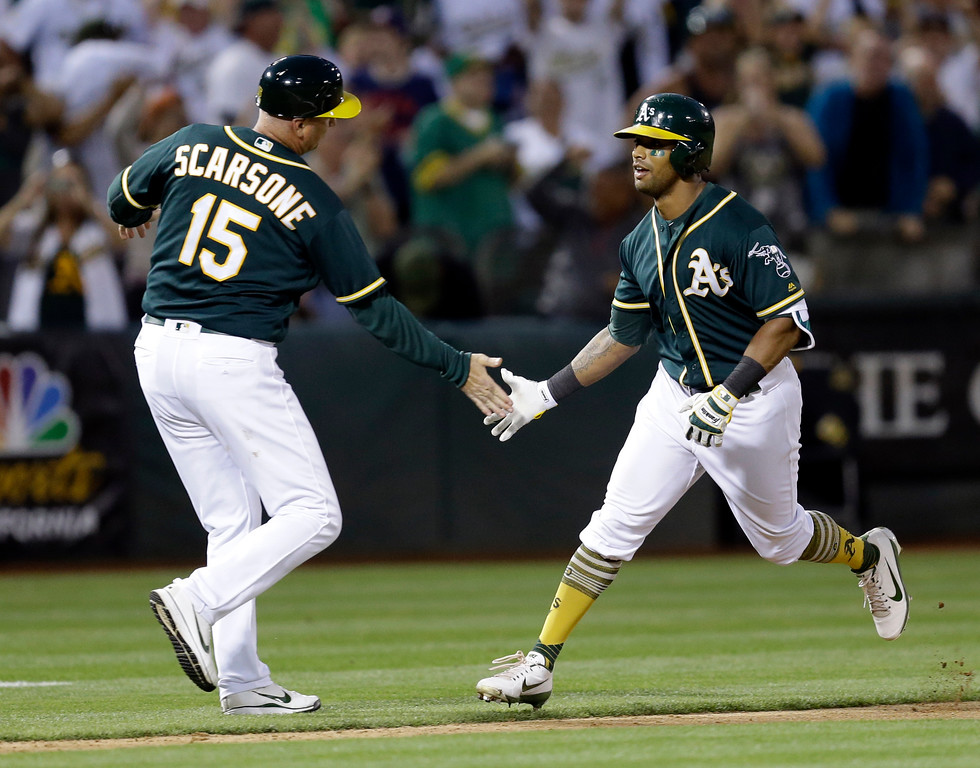 . Oakland Athletics\' Khris Davis, right, is congratulated by third base coach Steve Scarsone after hitting a two-run home run off Cleveland Indians\' Bryan Shaw during the ninth inning of a baseball game Saturday, July 15, 2017, in Oakland, Calif. The A\'s won 5-3. (AP Photo/Ben Margot)